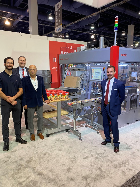 GOYA食品和SOMIC官员在PACK Expo的第一天宣布了一项包装机械协议。从左到右:Jason Unanue, GOYA产品经理;Ryan Schumacher, SOMIC东岸销售经理;戈雅的执行工厂经理Disney Arrubla;和Peter Fox, SOMIC的销售高级副总裁